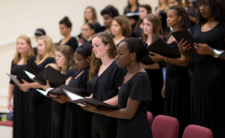 group of all women wearing black sining in choir rehearsing with sheet music