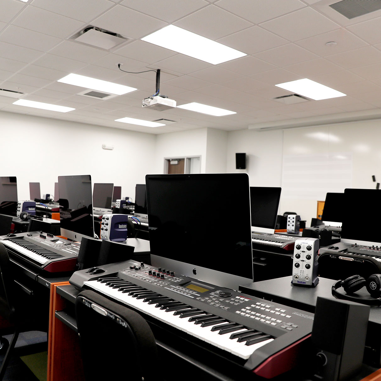music lab filled with mac computers headphones keyboards and other equipment