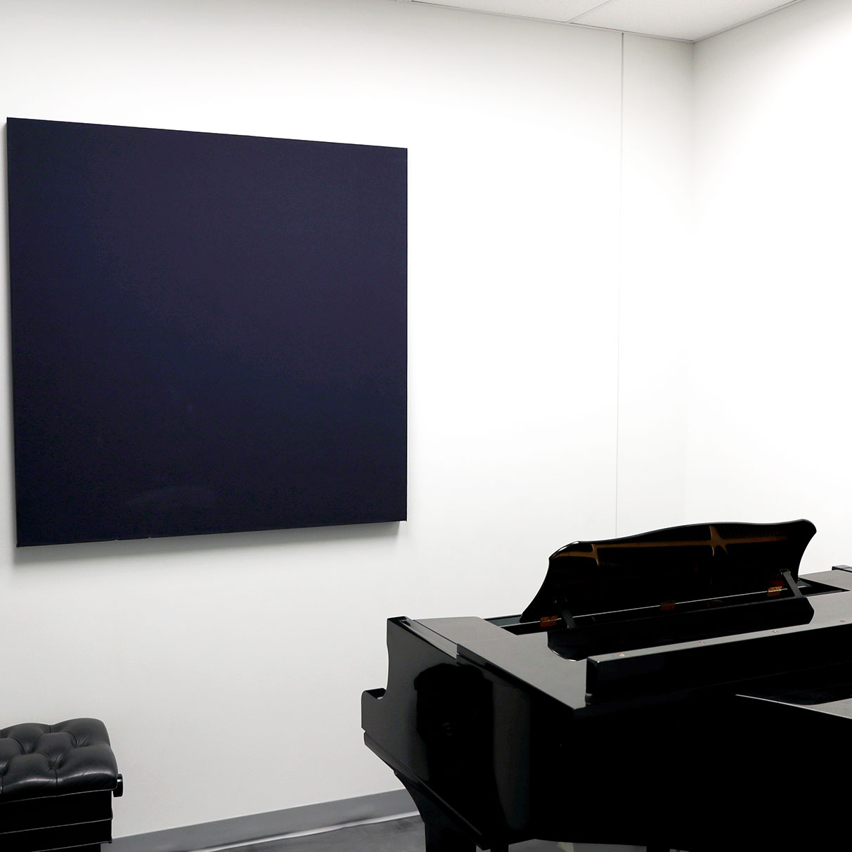 practice room has a black grand piano with a leather stool to sit with sound proofing on walls