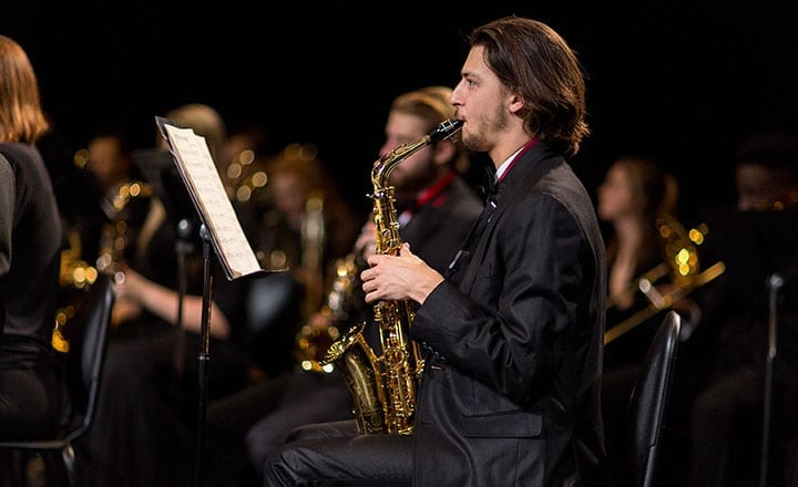 wind ensemble man in all black playing saxophone in concert