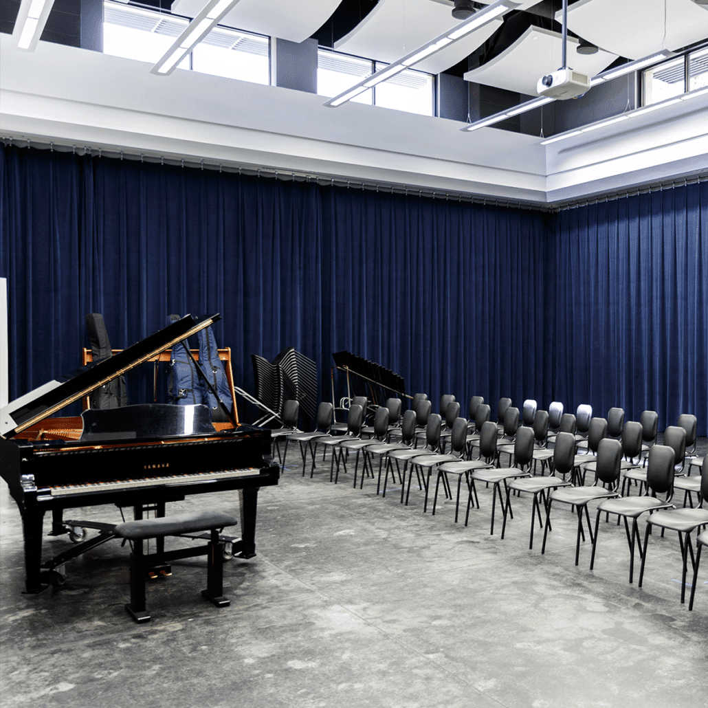empty choral hall with piano and chairs