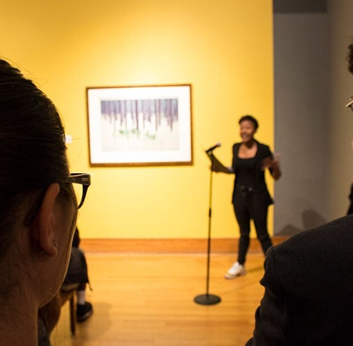 a young girl is standing up in front of crowd storytelling in a yellow room