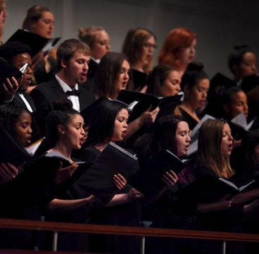 choir in all black performing for an audience
