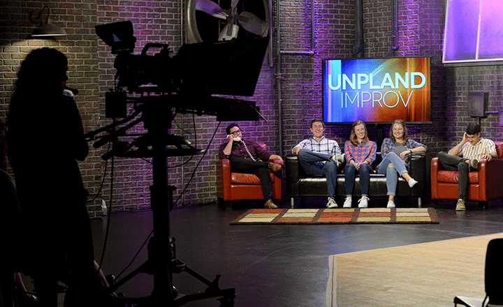 unpland improv on set and behind the scenes with students sitting on couch doing a skit